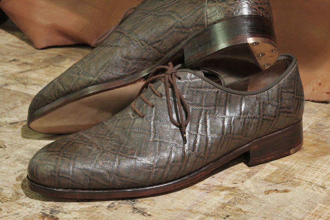 Buty wymagające reperacji. Widoczne są dziury w przetartych na wylot zelówkach oraz zużyte mosiężne fleki.